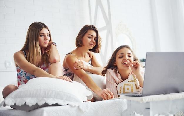 Film kijken op laptop en popcorn eten. gelukkige vrouwelijke vrienden die plezier hebben op een pyjamafeestje in de slaapkamer.