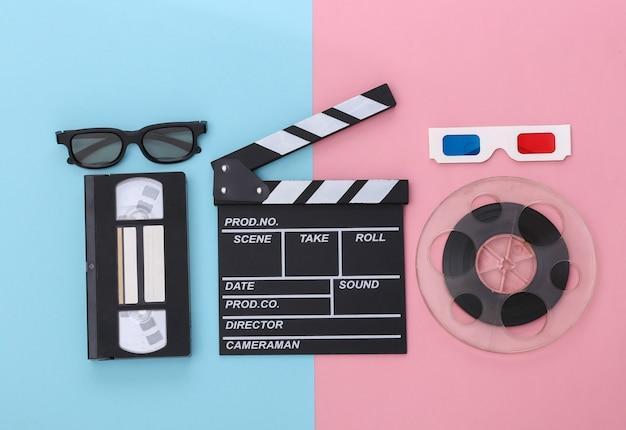 Film klepel bord en accessoires op roze blauwe pastel achtergrond. retro jaren 80. bioscoopindustrie, entertainment. bovenaanzicht
