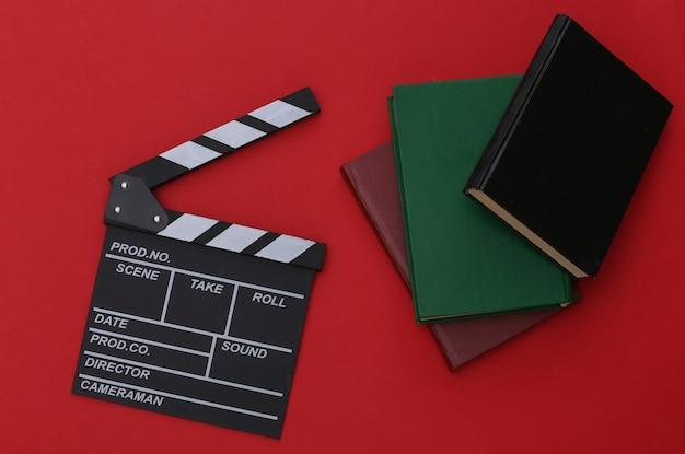 Film klepel bord en boeken op rode achtergrond. film per boek. bioscoopindustrie, entertainment. bovenaanzicht