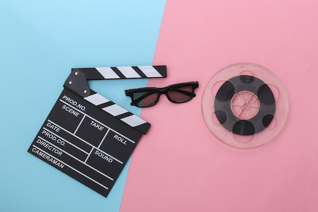 Film klepel bord en filmrol, 3d-bril op roze blauwe pastel achtergrond. bioscoopindustrie, entertainment. bovenaanzicht