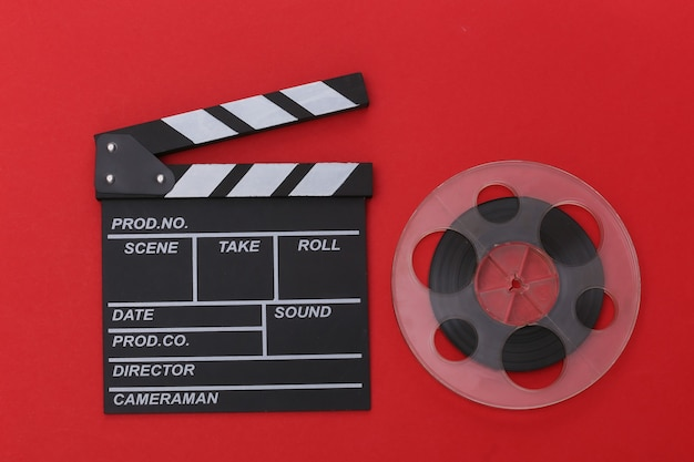 Film klepel bord en filmrol op rode achtergrond. bioscoopindustrie, entertainment. bovenaanzicht