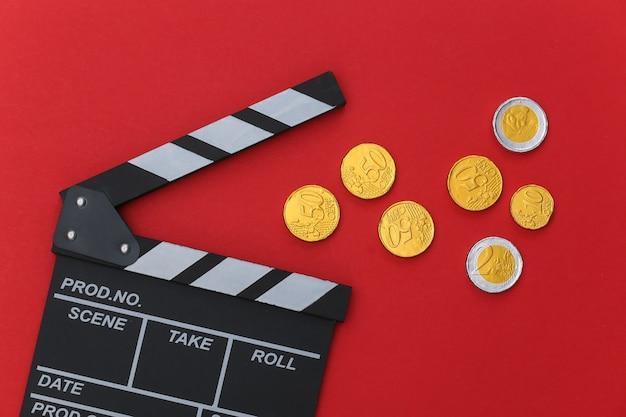 Film klepel bord met munten op rode achtergrond. bioscoopindustrie, entertainment. bovenaanzicht
