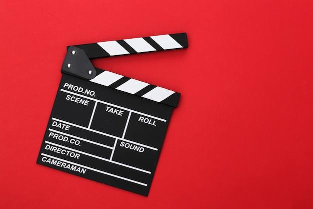 Film klepel bord op rode achtergrond. bioscoopindustrie, entertainment. bovenaanzicht
