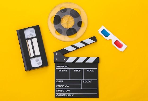 Film klepel bord, videocassette en filmrol, 3d-bril op gele achtergrond. bioscoopindustrie, entertainment. bovenaanzicht
