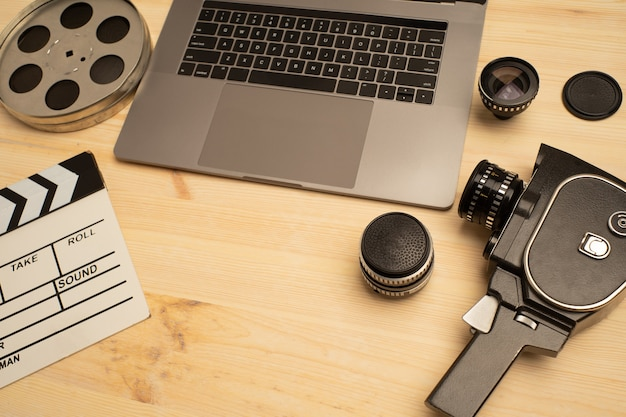 Film klepel, laptop en camera op houten tafel, bovenaanzicht