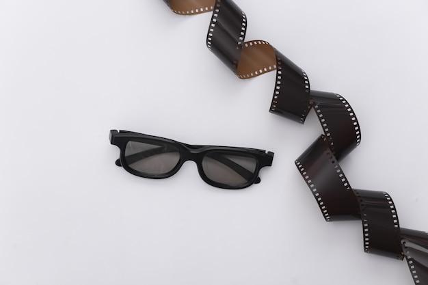Film tape en 3d-bril op witte achtergrond. ã â¡inema, entertainment-industrie. bovenaanzicht