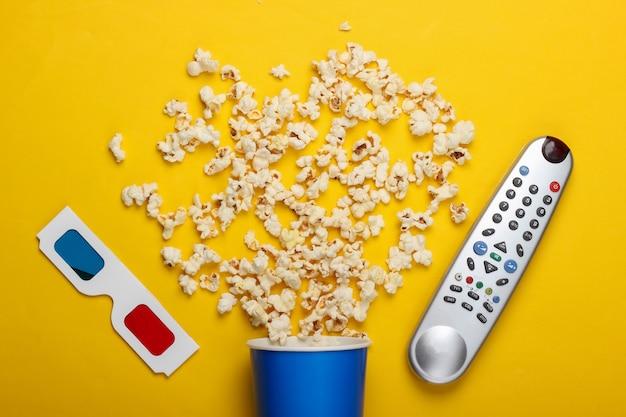 Film tijd. kartonnen emmer met popcorn, tv-afstandsbediening en stereoscopische anaglyph wegwerp papieren 3d-bril op geel oppervlak. bovenaanzicht