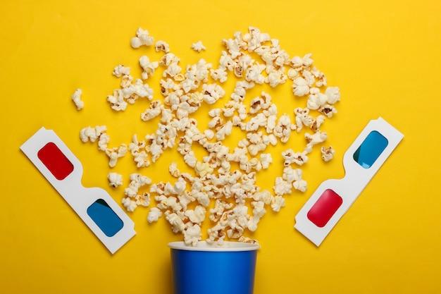 Film tijd. kartonnen emmer popcorn en stereoscopische anaglyph wegwerp papieren 3d-bril op geel oppervlak. bovenaanzicht