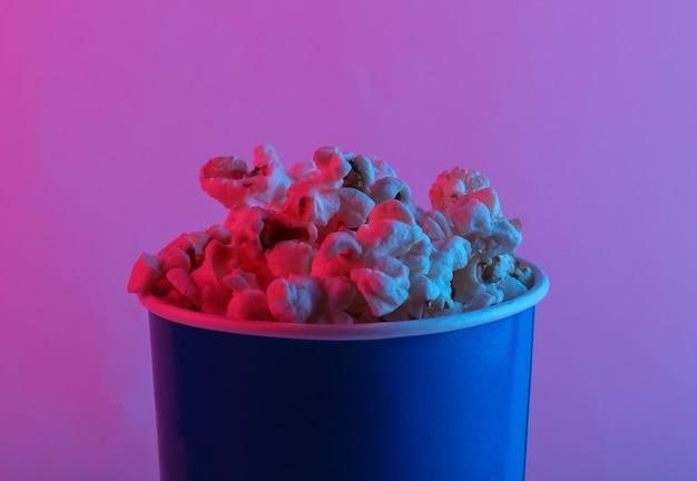Film tijd. kartonnen emmer popcorn in roze blauw verloop neonlicht.