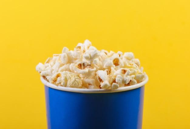 Film tijd. kartonnen emmer popcorn op gele achtergrond.