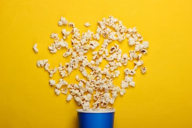 Film tijd. kartonnen emmer popcorn op gele ondergrond. bovenaanzicht