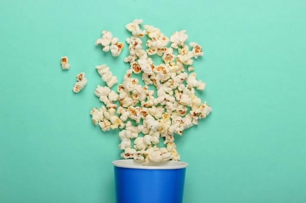 Film tijd. kartonnen emmer popcorn op mintgroen oppervlak. bovenaanzicht