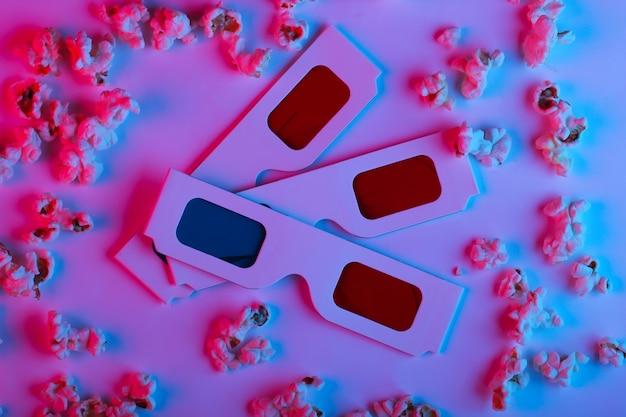 Film tijd. stereoscopische anaglyph wegwerp papieren 3d-bril met popcorn in roze blauw gradiënt neonlicht.