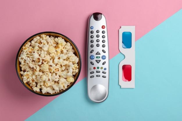 Film tijd. stereoscopische anaglyph wegwerp papieren 3d-bril, popcorn en tv-afstandsbediening op blauw roze oppervlak. bovenaanzicht