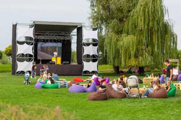 Filmdag. mensen kijken naar een film op straat op een groot scherm, zittend op een groen grasveld en in comfortabele tassen