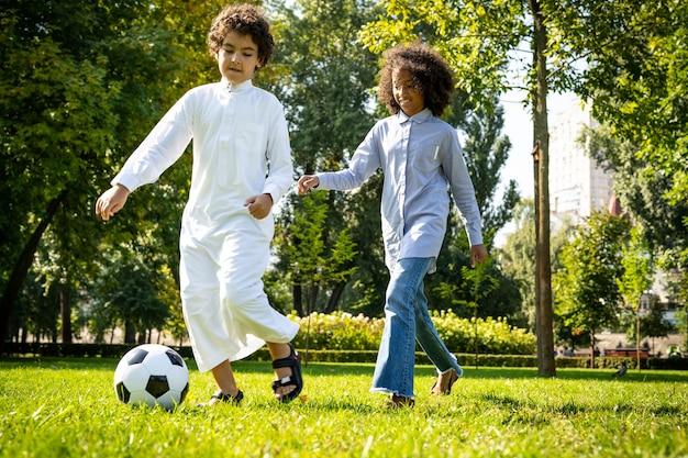 Filmisch beeld van een familie uit de emiraten die tijd doorbrengt in het park. broer en zus voetballen in het gras