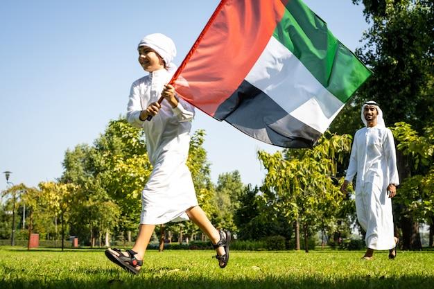 Filmisch beeld van een familie uit de emiraten die tijd doorbrengt in het park. jonge man aan het voetballen in het gras