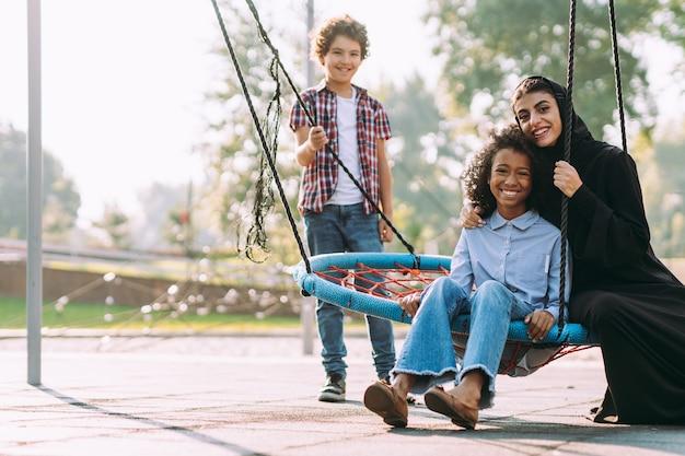 Filmisch beeld van een vrouw uit de emiraten met haar kinderen die plezier hebben op de speelplaats