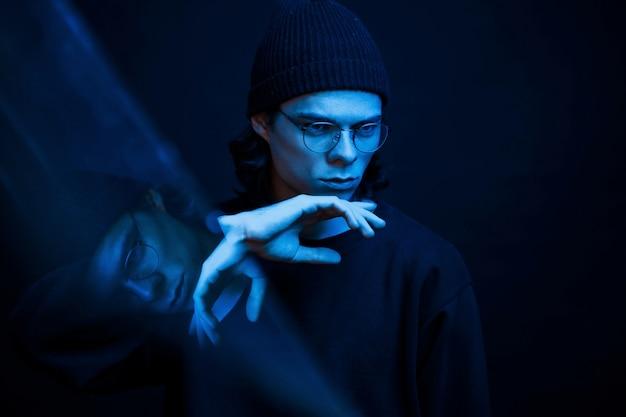 Filmisch effect. studio opname in donkere studio met neonlicht. portret van ernstige man