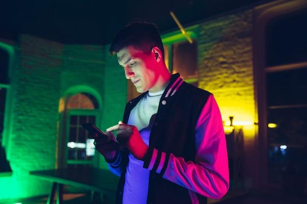 Filmisch portret van een knappe jongeman in een stijlvolle muzikant in een neonverlichte kamer