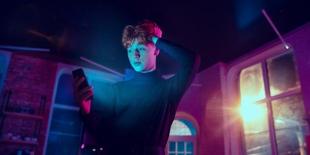 Filmisch portret van knappe jongeman in neonverlicht interieur