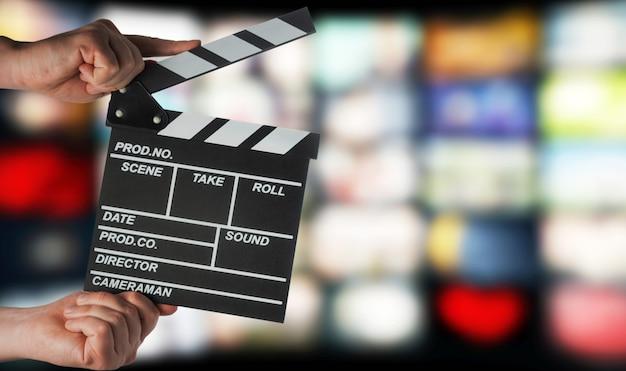 Filmklapper in handen op de achtergrond van tv-schermen