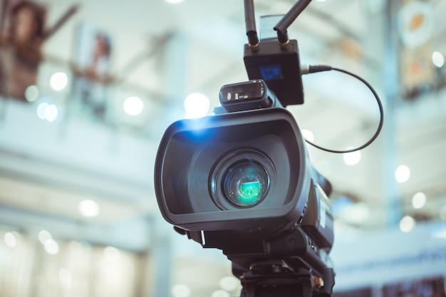 Filmlens van videocamera die film ontspruiten die van grote opening in conferentiezaal het stromen