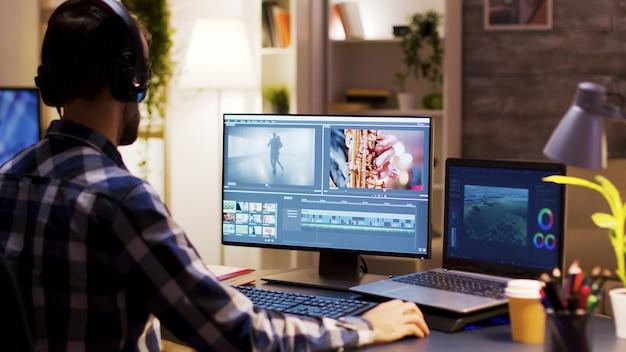 Filmmaker wijst naar de monitor in het thuiskantoor terwijl hij aan de postproductie voor een film werkt. video-editor die een koptelefoon draagt.