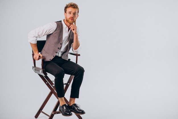 Filmregisseur zittend in een stoel en kijkend naar de camera