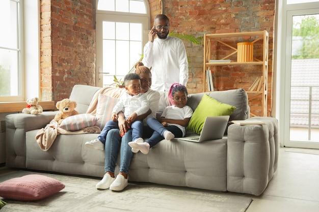 Filmtijd jonge en vrolijke afrikaanse familie tijdens quarantaine-isolatie tijd doorbrengen