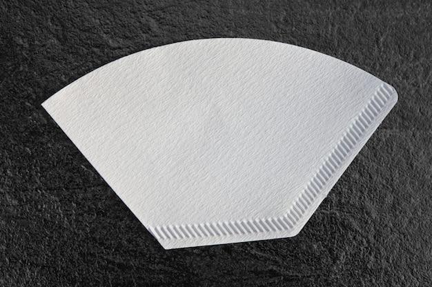 Filterpapier. geïsoleerd op een donkere tafelachtergrond met uitknippad voor alle soorten en merken filterkoffiezetapparaten
