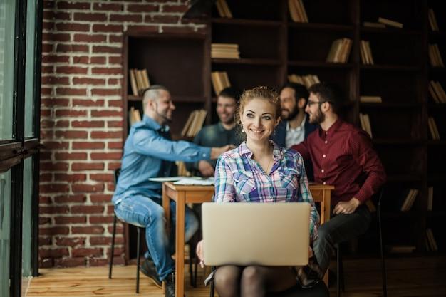 Financieel administrateur vrouw met laptop op achtergrond van zakelijke partners handshaking
