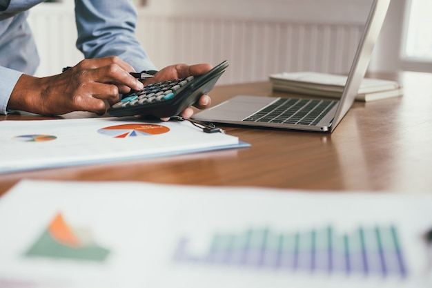 Financieel adviseur gebruikt calculator om omzet en budget te berekenen, accountant doet boekhouding, boekhouder maakt berekening