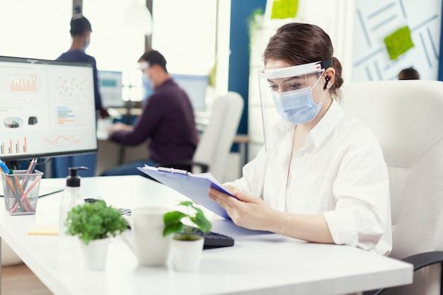 Financieel adviseur met draadloze koptelefoon die financiële statistiek controleert in een druk kantoor met gezichtsmasker. werknemers met vizieren die in de werkruimte van een bedrijfsbedrijf werken en de analyse van sociale afstand respecteren