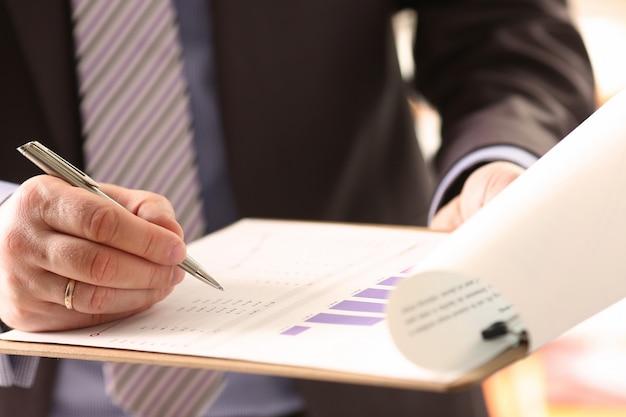 Financieel auditor die het berekenen van document ondertekent
