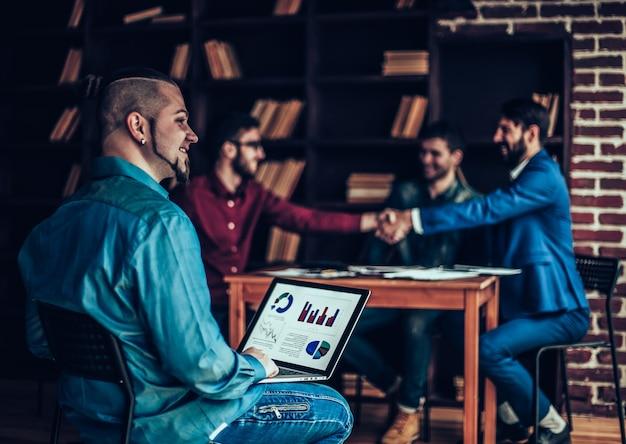 Financieel beheerder werkt met financiële grafieken op de achtergrond van zakenpartners die de handen schudden in een modern kantoor
