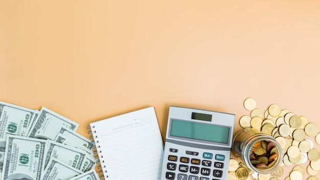 Financieel concept, rekenmachine en notebook, munten in glazen flessen met dollarbiljetten op oranje.