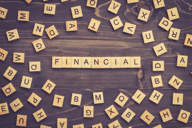 Financieel woord hout blok op tafel voor business concept.