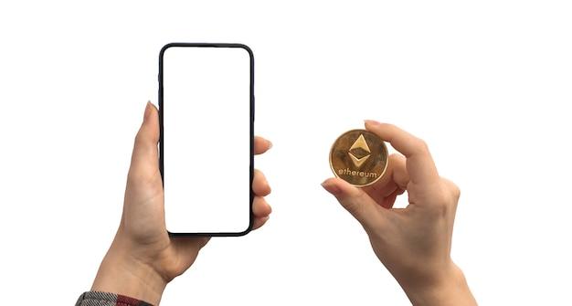 Financiële betaling met ethereum eth en mobiele telefoon, leeg wit schermmodel, handen met cryptocurrency-muntstuk dat op een witte achtergrondfoto wordt geïsoleerd