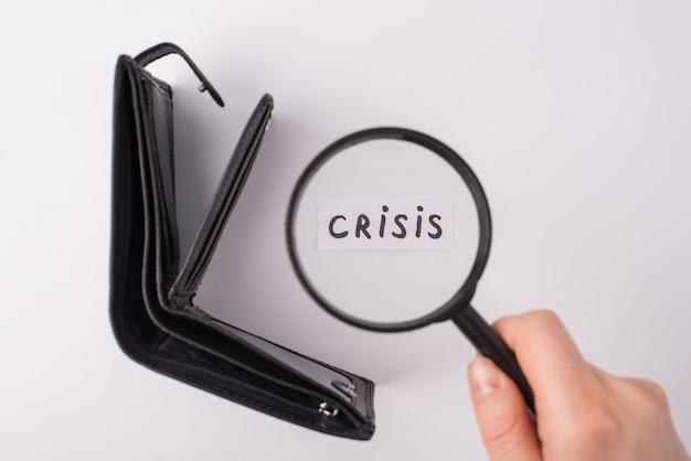 Financiële crisis 2020 concept. boven boven bovenaanzicht foto van vrouwelijke hand met lupa over woordcrisis en lege open portemonnee over grijze achtergrond