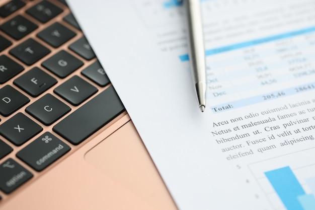 Financiële documenten en pen zijn op laptop toetsenbord. zakelijke rapporten online concept