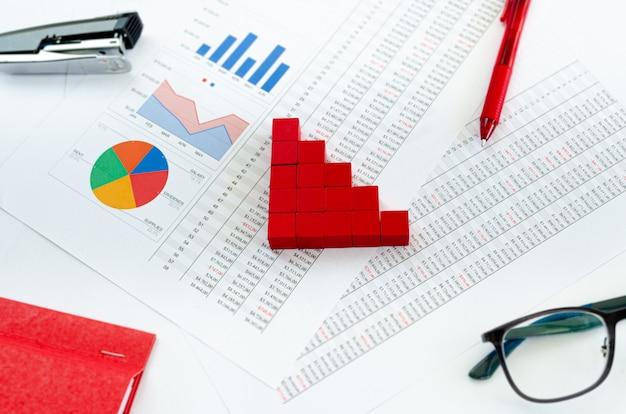 Financiële documenten, met groene blokjes gerangschikt in een kolomgrafiek als een concept voor uitgaven, kapitaal of activa