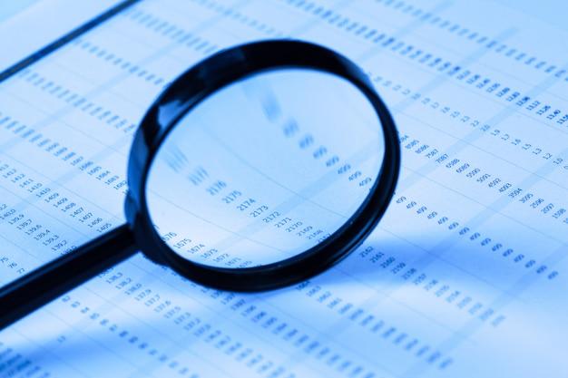 Financiële documenten met vergrootglas