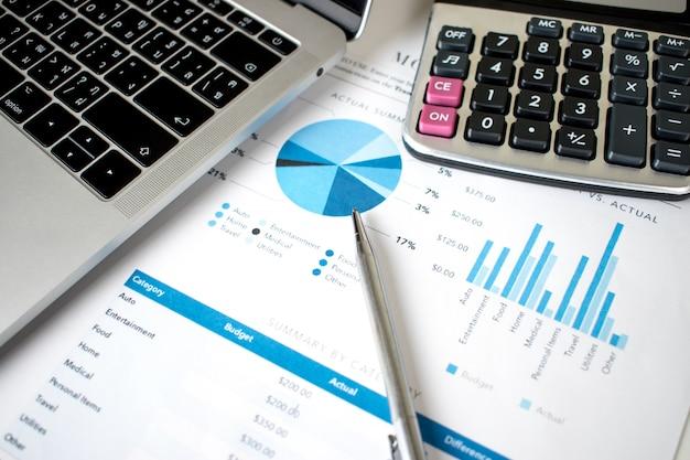 Financiële grafiek met laptop en calculator op het bureau
