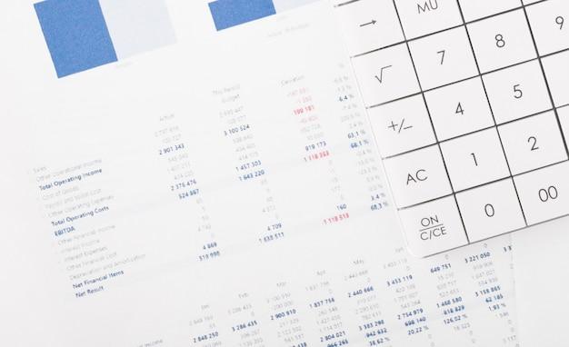Financiële grafieken en een rekenmachine op het bureau van de accountant. winst, belastingen en salarissen van werknemers berekenen.