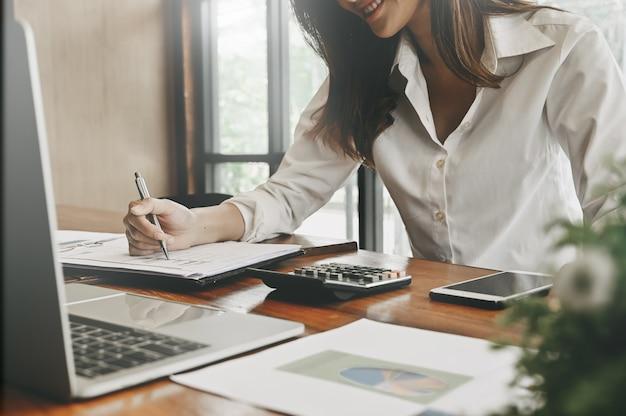 Financiële huisplanning, vrouw die aan notitieboekjedocument met de levering van bureaunefinanciering op bureau werkt.