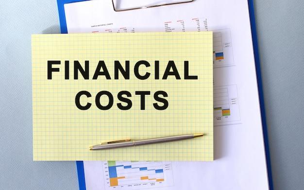 Financiële kosten tekst geschreven op kladblok met potlood. kladblok op een map met diagrammen. financieel concept.