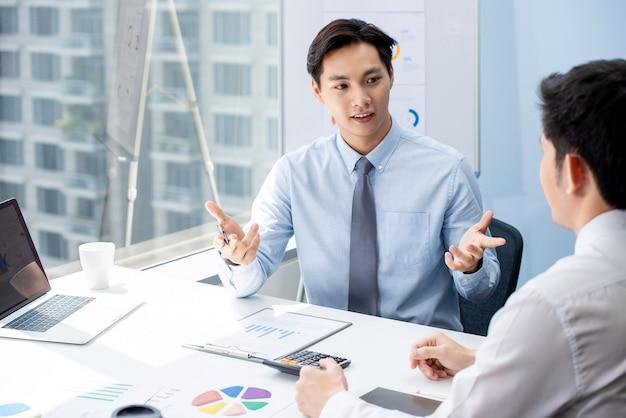 Financiële makelaar die bedrijfsgegevens onderzoekt aan zijn klant