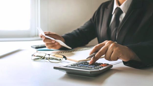 Financiële medewerkers berekenen bedrijfswinsten op basis van grafieken op hun bureau thuis, financiële ideeën en audits.