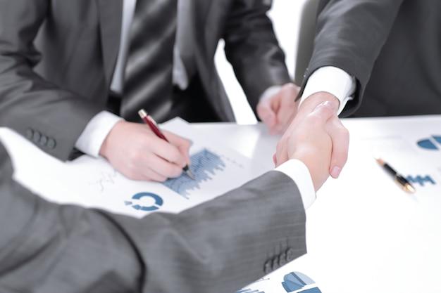 Financiële partners die een bureau de hand schudden.